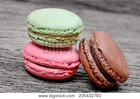 Colorful macaroons on wooden table close up