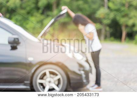Blurred of broken down car and asian woman calling car mechanic