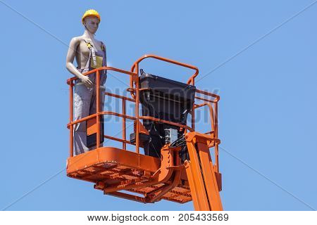 Hydraulic mobile construction platform elevated towards a blue sky with false construction workers . dummy man .