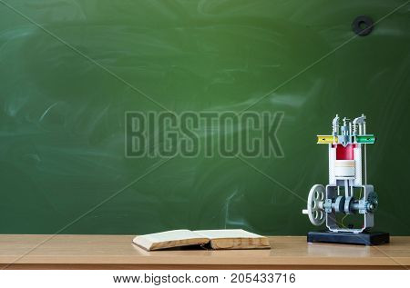 Teacher student on engineer desk table. Education background. Education concept. Copybook and education model of internal combustion engine on the table.