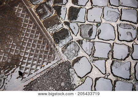 Manhole cover on old cobblestone street on wet stone pavement. Vintage sewer system utility on old style brick road in Rome Italy.