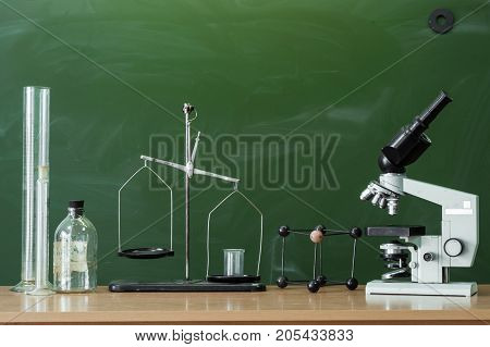 Teacher or student desk table. Education background. Education concept. Microscope beakers vials and scales on the table. Chemistry or biology lesson.