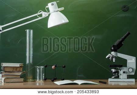 Teacher or student desk table. Education background. Education concept. Microscope copybook beakers stacked books and lamp on the table. Chemistry or biology lesson.