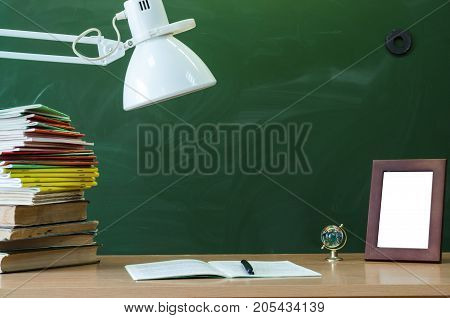 Teacher or student desk table. Education background. Education concept. Globe stacked books open book (copybook) handbook and photo frame on the table.