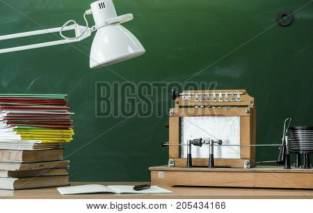 Teacher student or electrician engineer desk table. Education background. Education concept. Education models of electric chain model stacked books copybook and lamp on the table.