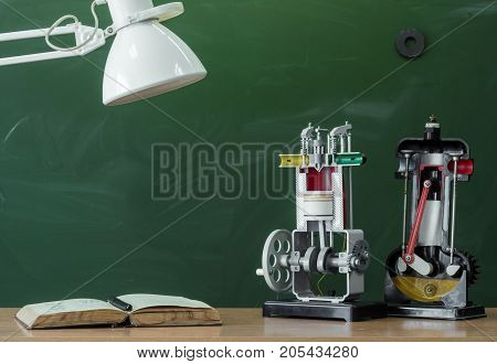 Teacher student or engineer desk table. Education background. Education concept. Textbook and education model of internal combustion engine on the table.