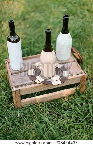 handcraft, summer, vacation concept. three wine and champagne bottles covered by half with white and light pink paints for creating popular game called ringo