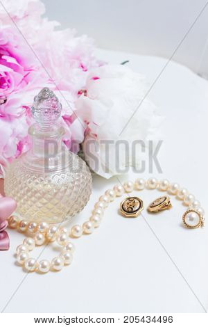 Lfestyle with pink peony flowers, glamour bottles and jewellery close up
