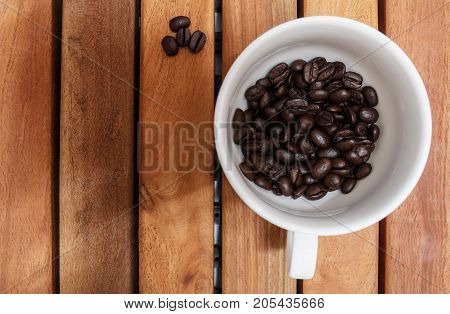 Roasted coffee beans in white cup on a floor wooden
