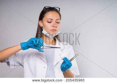 Serious medical woman holding cotton wool with tongs, preparing for manipulations