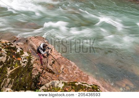 hobby, high qualification, nature concept. professional photographer is at work, standing with tripod on the rocky coast nearby with river with choppy waters that flowing away very fast