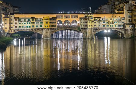 FLORENCE, ITALY - SEPTEMBER 18, 2014: Ponte Vecchio and Arno river by night in Florence. This world famous bridge dates back to 1345.