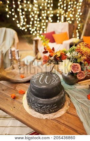 holidays, sweeties, party concept. popular goodies for celebration any occasion, two tier cake of unexpected black colour, with initials of some persone, it placed near the flowers