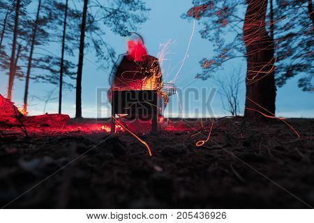 Burning firewood in the barbecue against the abstract person silhouette at night.