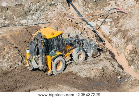 Tractor Excavator With Bucket Rides Running Through Mud Lands Setting, View From The Height