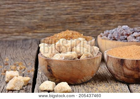 Different kinds of sugar in a bowls on wooden background close-up