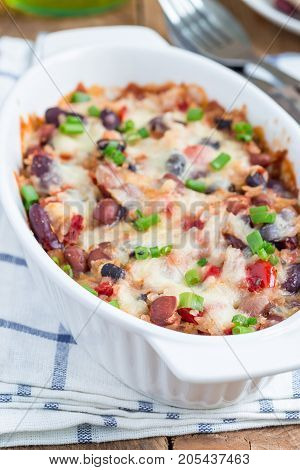 Baked rice casserole with different kinds of beans cheese and paprika in a white ceramic baking dish vertical