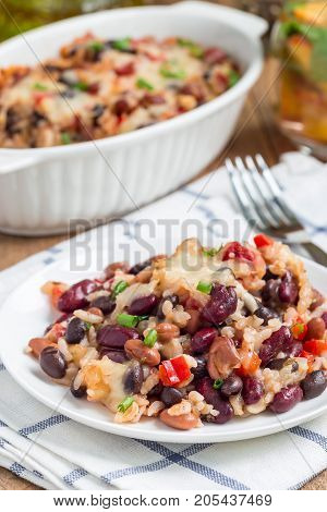 Baked rice casserole with black beans pinto beans kidney beans and cheese on a white plate vertical