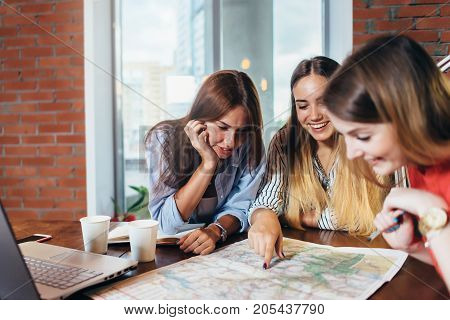 Three female students doing geography homework together at home.