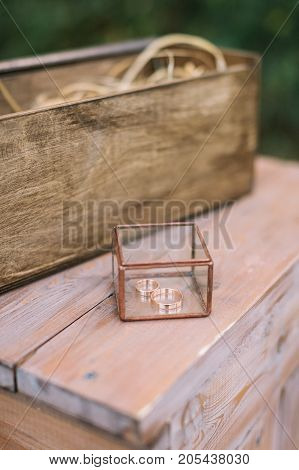 jewelry, wedding, design concept. in wonderful small box made almost of transparent glass there are two golden engagement rings, one for bride and another for fiance