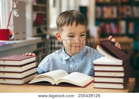 Curious boy is siting at the table and open a book turning his head at the left. European boy wearing a shirt is exploring many books in a library. Pupil loves lecture, preparing for school.