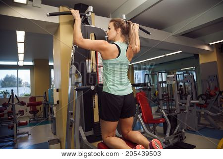 Young Fitness Woman Execute Exercise With Exercise-machine In The Gym.