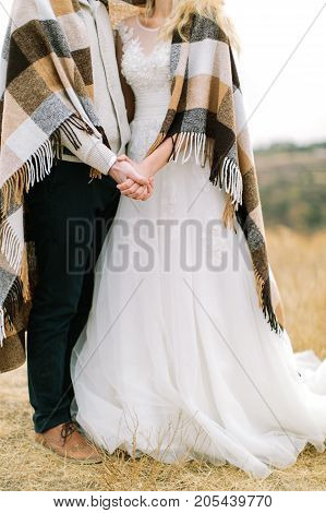 marriage, nature, relationships concept. fiance and bride wearing costume and wedding dress standing hugged each other and covered by warm comfortable plaid with creamy squares