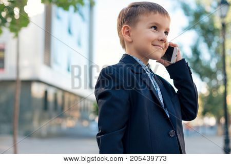 Concept future businessman. Business meeting. Low angle of future businessman in dark blue jacket holding white phone to ear listening to somebody, urban background.