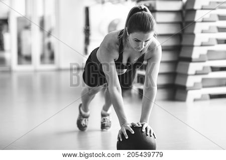 Young Strong Girl Doing Plank With The Ball In The Gym. Black And White Photo