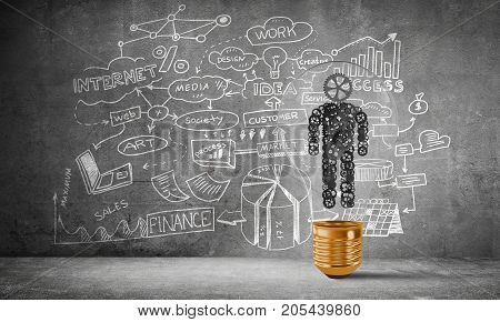 Lightbulb with human from gears inside placed against sketched business plan on grey wall. 3D rendering.
