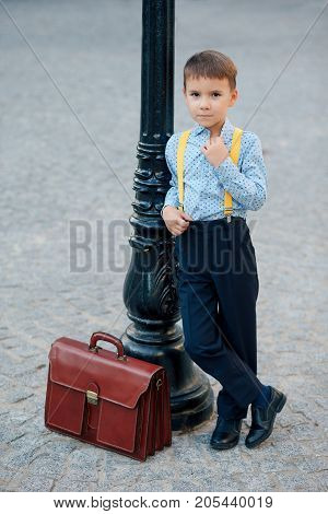 Concept future bank clerk. Full length boy portrait in dark blue pants, baby blue shirt and yellow straps, standing on pedestrian street with braun briefcase looking to camera, urban background.