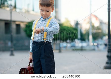 Concept future businessman. Boy portrait in dark blue pants, baby blue shirt and yellow straps, standing on pedestrian street with braun briefcase looking to his watch, urban background.