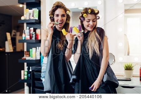 Young pretty girls in capes with hair curlers goofing around in beauty salon. Girlfriends showing devil horn and piece gesture with rollers on fingers having fun together.