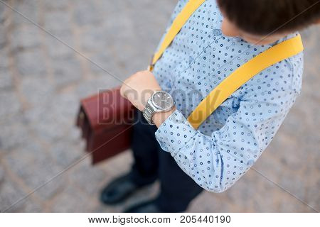 Silver watch on the hand of future businessman in blue shirt, with brifcase and yellow suspenders. Time on wrist watch. Man with clock checks the time. Hand with clock.