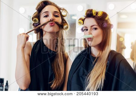 Two cute girlfriends in black cape wearing curlers making moustache out of their hair and roller in hairdressing salon.