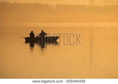 Orange sunrise on the lake. Silhouettes of two fishermen in a boat dawn fog
