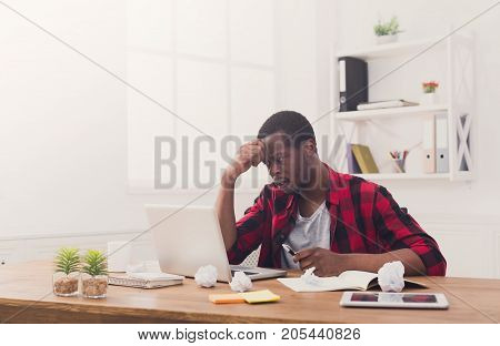 Stressed black businessman in office, in casual, work with laptop, solving a problem