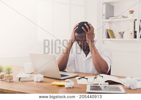 Stressed black businessman in office, work with laptop, solving a problem