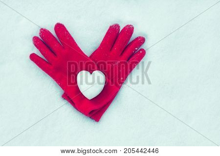 snow heart on red gloves. Winter holidays, Valentine's day, love symbol concept. Valentine's Day greeting card top view with copy space. Flat lay