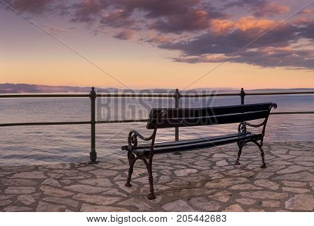 An empty bench by the sea in Opatija Croatia waiting for some tired passer-by
