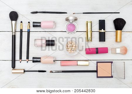 cosmetics laid out on a white wooden background in a geometric style. Flat lay