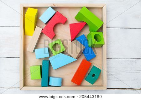 Wooden kids toys multicolor in wooden box. Flat lay
