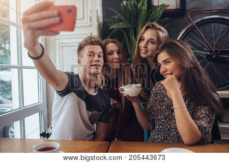 Group of cute teenagers taking selfie with cellphone while sitting in a restaurant with interior in retro style.