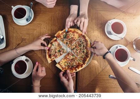 Top view of hands taking pizza slices from a plate standing on a table with tea cups around.