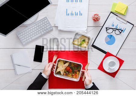 Eating business lunch at working place. Healthy food in office. Diet restaurant meals delivery in foil boxes: scrambled eggs with vegetables. Top view, flat lay