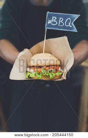 Street fast food festival, hamburger cooked at barbecue outdoors. Cookout american bbq food, closeup in chef's hand in craft paper with copy space for text