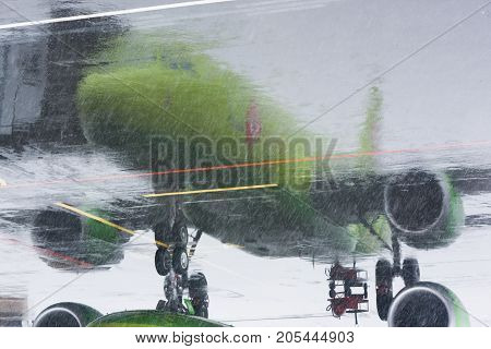 Green passenger airplane reflected on the wet from the rain and snow asphalt at the airport