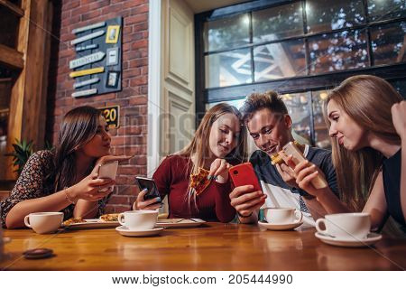 Young people using their mobile phones sitting around the table having a meal in modern stylish cafe.
