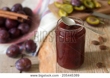 Homemade plum jam or confiture in a glass jar, and fresh plums on a wooden background. Rustic style, selective focus.