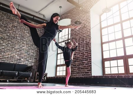 Smiling mother and cute little daughter in black sportswear doing standing split leg stretching exercise keeping balance.